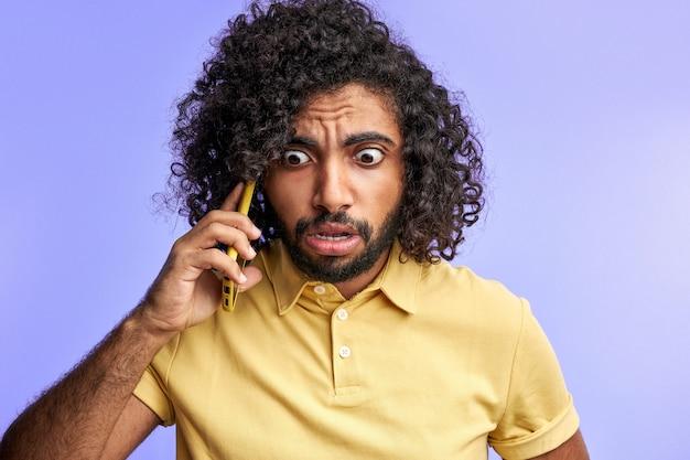 Man in shock na het krijgen van nieuws over ongeval op telefoon, neerkijkt geïsoleerd in de studio