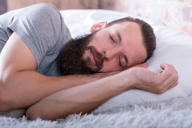 Man in slaap portret. gezondheidszorg. gemoedsrust. jonge, bebaarde man slapen met kalme gelaatsuitdrukking.