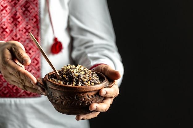 Man in slavische shirt met kom met traditionele kutia