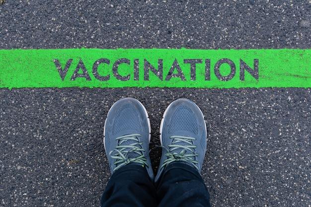 Man in sneakers die naast een groene lijn staat met de tekst vacctinatie, pandemisch eindconcept