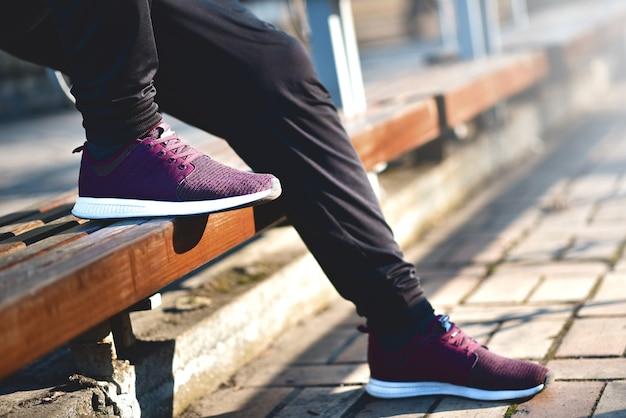 Man in sneakers loopt op een zonnige dag over straat