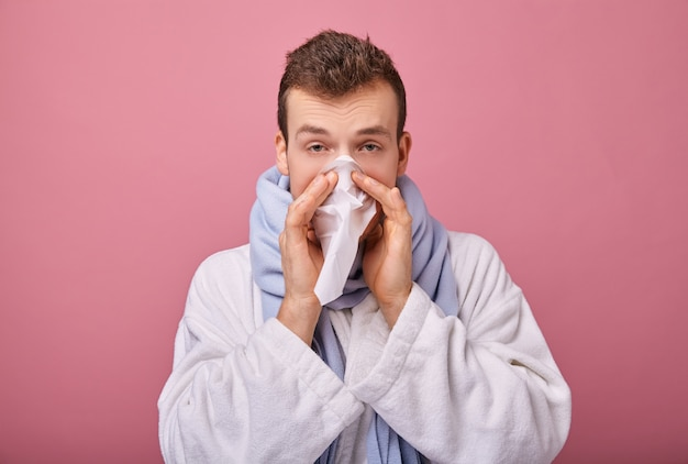 Man in sneeuwwitte mantel met blik van zieke staat bevroren en blaast zijn neus in servet