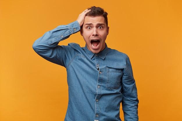 Man in spijkerblouse houdt zijn hoofd met één hand vast, toont een luide kreet, mond is wijd open