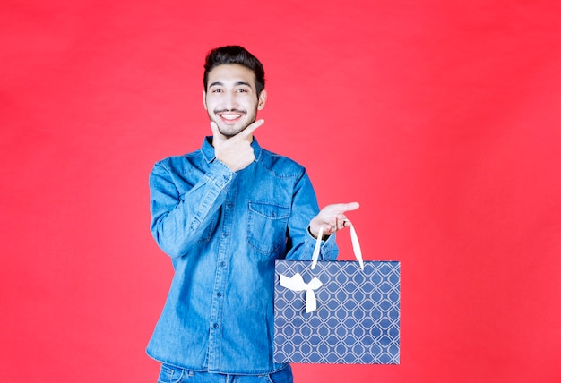 Man in spijkerbroek met een boodschappentas en ziet er attent uit.