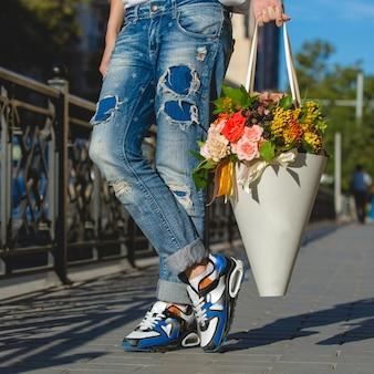 Man in spijkerbroek met een kartonnen boeket bloemen.
