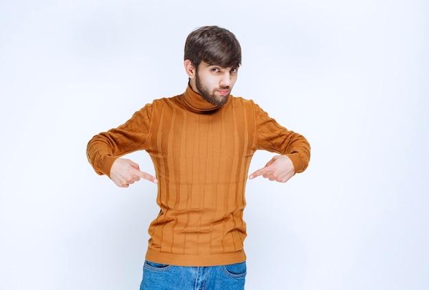 Man in spijkerbroek wijzend op zichzelf.