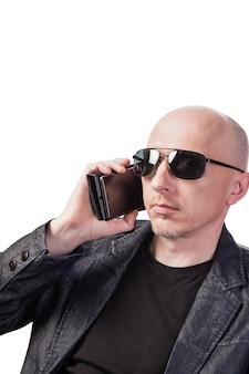 Man in spijkerjasje en het dragen van een zonnebril praten op een mobiele telefoon