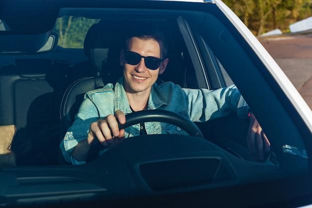 Man in spijkerjasje en zwarte bril lacht achter het stuur van een auto
