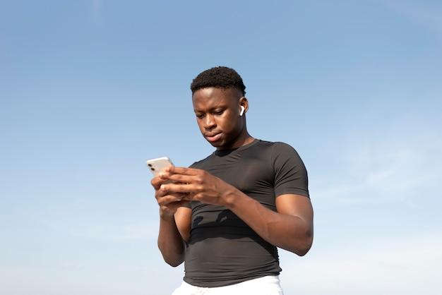 Man in sportkleding met zijn smartphone