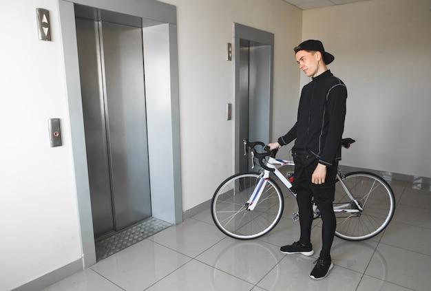 Man in sportkleding staat in een fiets huis en wachten op een lift