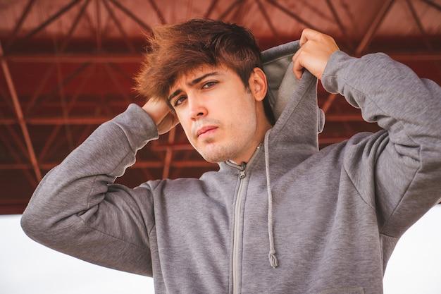 Man in sportkleding zijn hoodie aantrekken en kijken naar de camera attitude