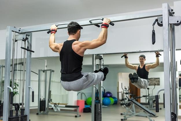 Man in sportschool doen enkele oefeningen op de dwarsbalk