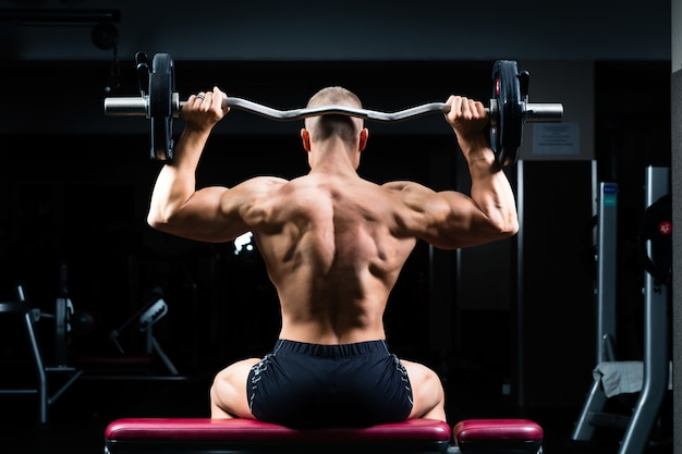 Man in sportschool of fitness center op halterbank