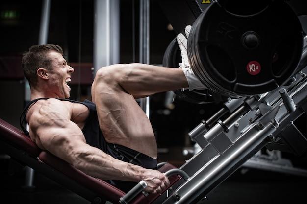 Man in sportschool training op legpress om zijn bovenbeenspieren te definiëren