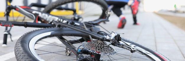 Man in sportuniform valt van fietsclose-up