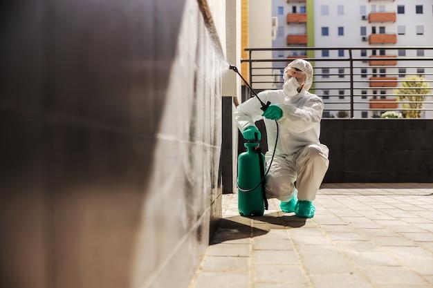Man in steriel beschermend uniform hurken en muur besproeien met ontsmettingsmiddel om verspreiding van het coronavirus te voorkomen.