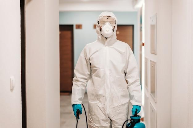 Man in steriel pak die hal van het gebouw desinfecteert.