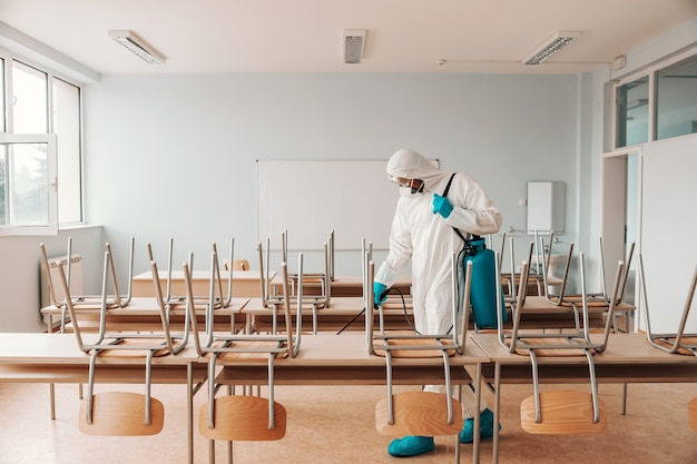 Man in steriel uniform, met handschoenen en masker met sproeier en sproeien met desinfecterende vloer in de klas.