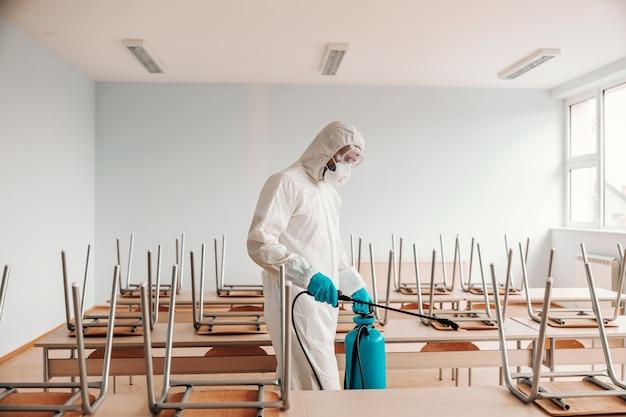 Man in steriel uniform, met handschoenen en masker met sproeier en sproeiend met desinfecterende tafels