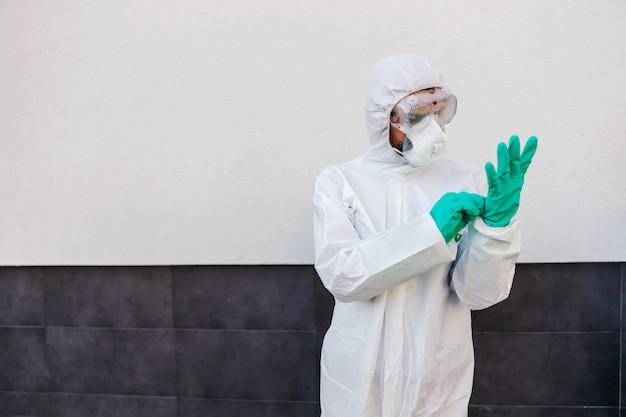 Man in steriele beschermende uniform buiten staan en rubberen handschoenen aantrekken. beschermingsformulier verspreiden coronavirus concept.