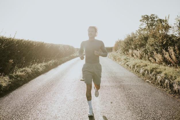 Man in stretchshirt loopt op het platteland bij zonsondergang