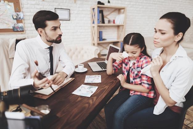 Man in stropdas praat met klanten, vrouw en dochter.