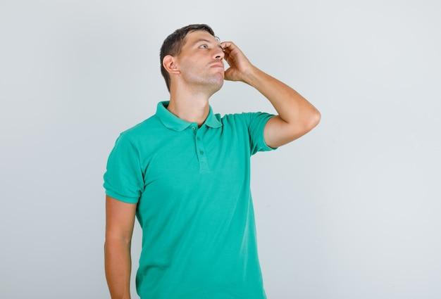Man in t-shirt opzoeken, hand in hand en op zoek attent, vooraanzicht.