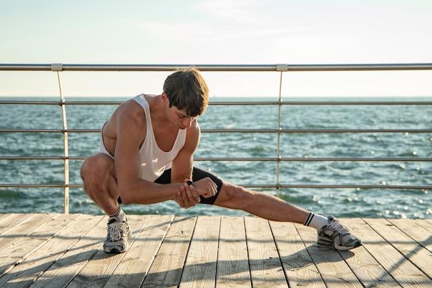 Man in tanktop trainen op het strand