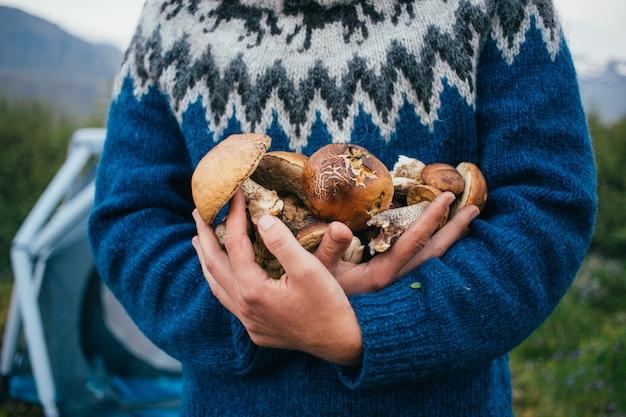 Man in traditionele blauwe wollen trui met ornamenten staat op camping in de bergen, houdt in de armen stapel van heerlijke en biologische, verse natuurlijke paddenstoelen uit het bos