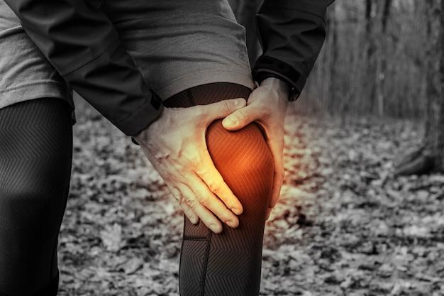 Man in trainingskleding kreeg een knieblessure tijdens het joggen in de buitenluchttraining. concept van sportblessure, hardlooptechniek, verkeerd rennen, peesontsteking, een grote belasting.