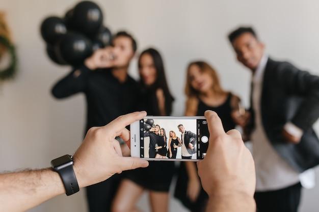 Man in trendy polshorloge met behulp van smartpone om foto te nemen op feestje
