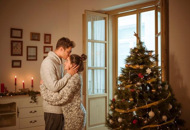Man in trui kussende vrouw op het voorhoofd