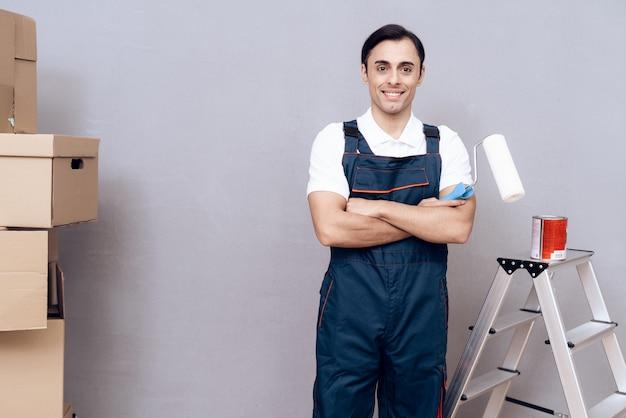 Man in uniform op grijze achtergrond met ladder.