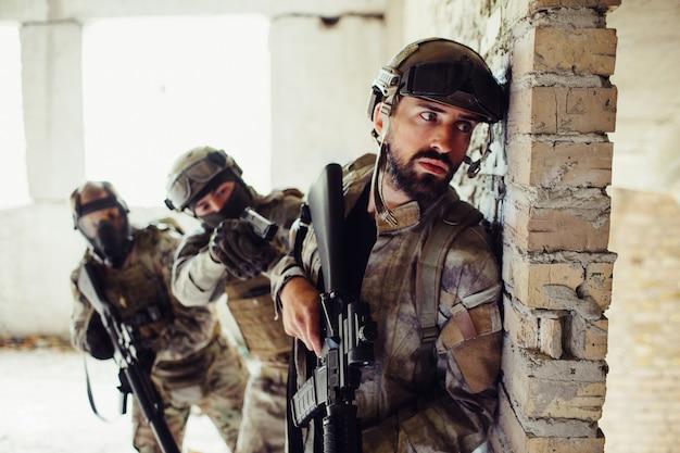 Man in uniform staan achter de muur en wachten.