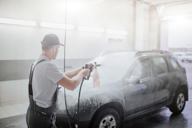 Man in uniform staat voor auto en wast het met water dat uit flexibele slang gaat. zwarte auto is bedekt met schuim. guy gaat het schoonmaken.