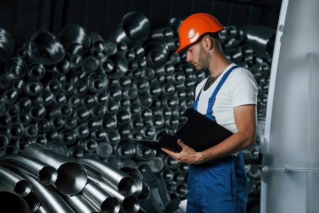 Man in uniform werkt aan de productie