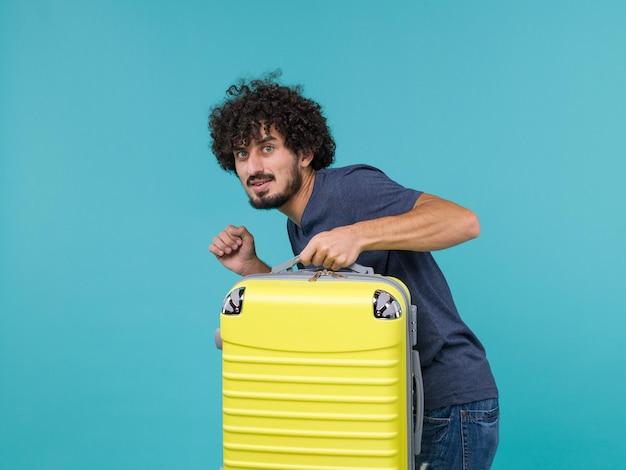 Man in vakantie in blauw t-shirt die stilletjes weggaat met zijn koffer op blauw