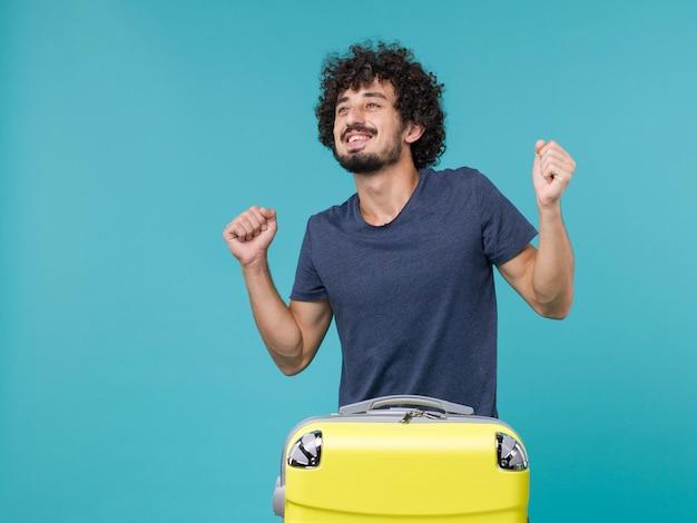 Man in vakantie in blauw t-shirt voelt zich gelukkig op blauw