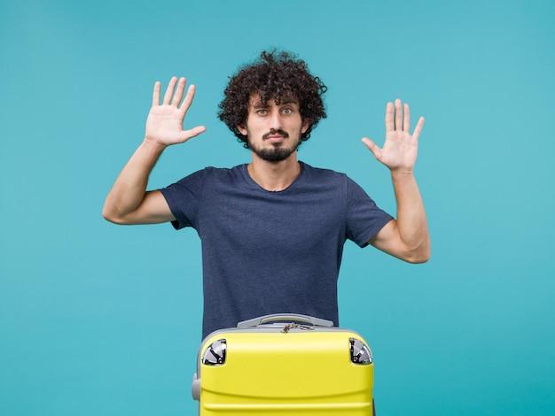 Man in vakantie in donkerblauw t-shirt poseren op lichtblauw