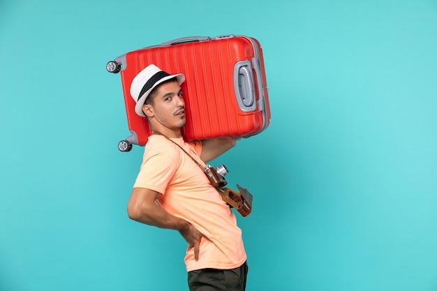 Man in vakantie met grote rode koffer op blauw