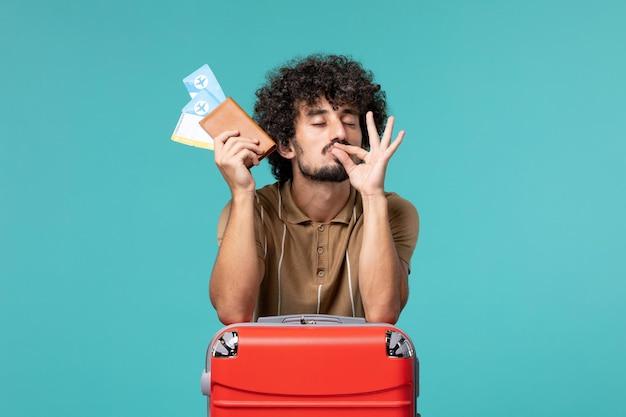 Man in vakantie met kaartjes en leunend tegen zijn rode tas op blauw