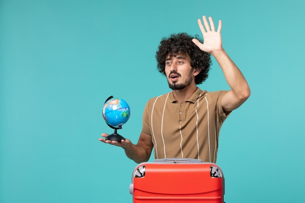 Man in vakantie met kleine wereldbol met rode tas zwaaiend op blauw