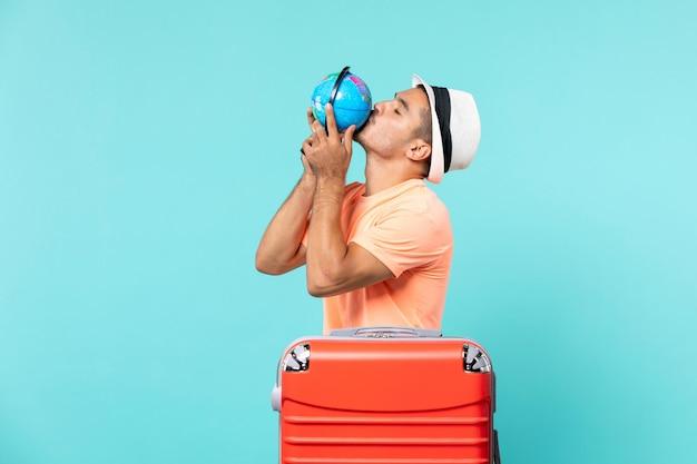 Man in vakantie met kleine wereldbol op blauw Gratis Foto