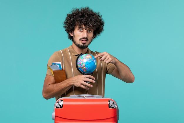 Man in vakantie met kleine wereldbol op blauw