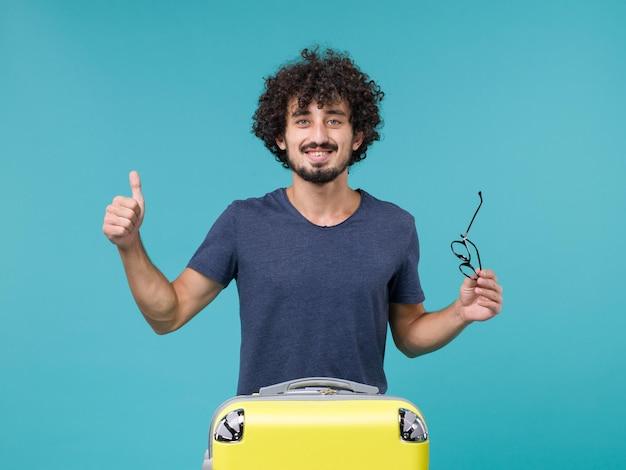 Man in vakantie met zijn grote gele koffer op blauw