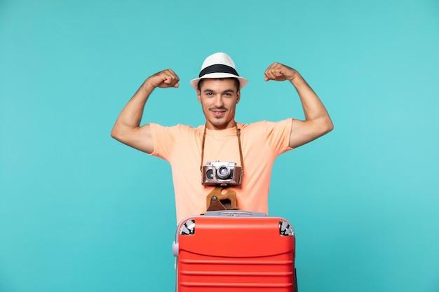 Man in vakantie met zijn rode koffer en camera buigend op blauw