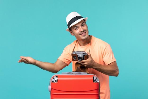 Man in vakantie met zijn rode koffer en camera op blauw