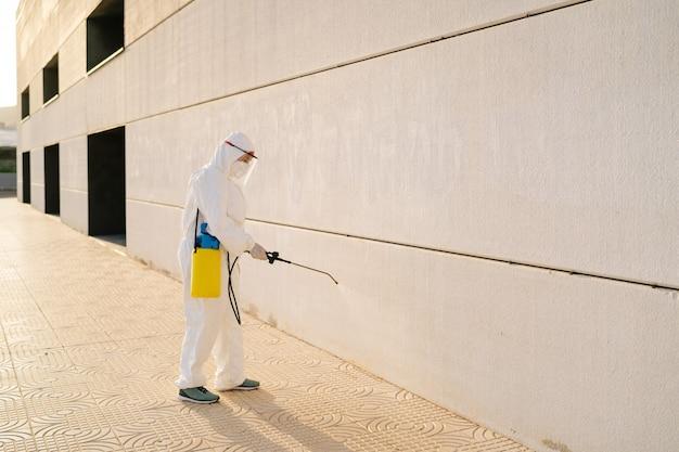 Man in virusbeschermend pak en masker die gebouwen van coronavirus desinfecteert met de sproeier. infectiepreventie en bestrijding van epidemieën. wereldpandemie.