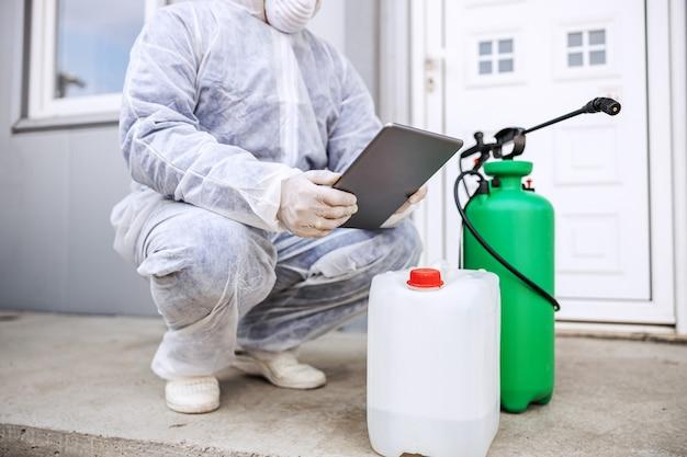 Man in virusbeschermend pak en masker kijkt en typen op tablet, gebouwen van coronavirus desinfecterend met de sproeier. epidemie.
