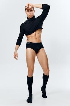 Man in volle groei opgeblazen torso bodybuilder fitness onderbroek en zwarte trui